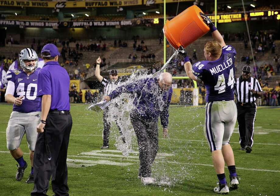 Head coach Bill Snyder of the Kansas State Wildcats is dunked with water by defensive end Ryan Mueller #44 during the final moments of the Buffalo Wild Wings Bowl against the Michigan Wolverines at Sun Devil Stadium on December 28, 2013 in Tempe, Arizona. The Wildcats defeated the Wolverines 31-14. Photo: Christian Petersen, Getty Images / 2013 Getty Images