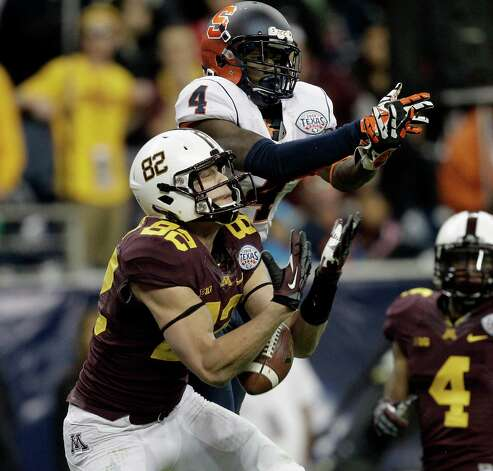 Drew Wolitarsky #82 of the Minnesota Golden Gophers has the ball go through his arms as he is defended by Brandon Reddish #4 of the Syracuse Orange in the fourth quarter at Reliant Stadium on December 27, 2013 in Houston, Texas. Photo: Bob Levey, Getty Images / 2013 Getty Images