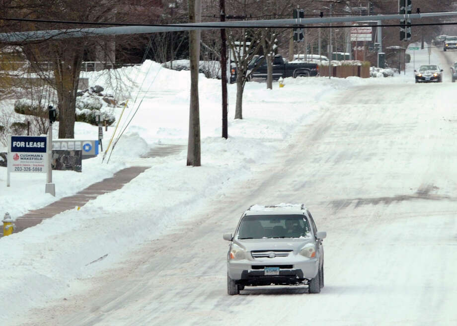 A vehicle drives along West Putnam Avenue during the snow storm that hit Greenwich, Conn., Friday morning, Jan. 3, 2014. Photo: Bob Luckey / Greenwich Time