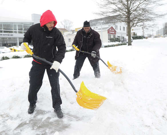 Miller Motorcars workers shovel snow from in front of the dealership on West Putnam Avenue in Greenwich during the snow storm that hit Green
