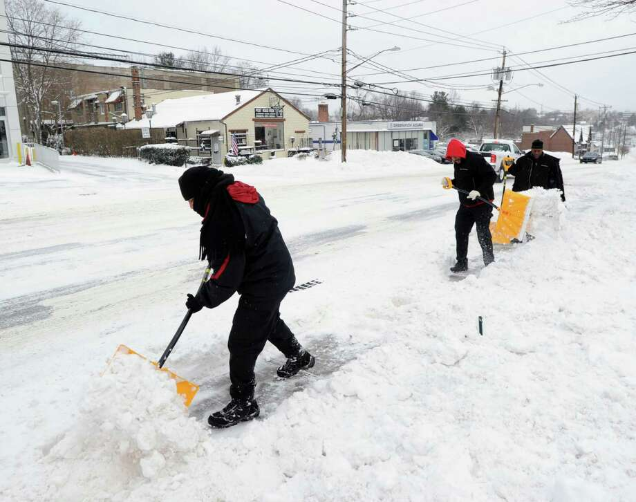 Miller Motorcars workers shovel snow from in front of the dealership on West Putnam Avenue in Greenwich during the snow storm that hit Greenwich, Conn., Friday morning, Jan. 3, 2014. Photo: Bob Luckey / Greenwich Time