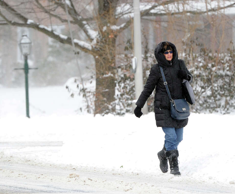 A woman walks along Field Point Road during the snow storm that hit Greenwich, Conn., Friday morning, Jan. 3, 2014. Photo: Bob Luckey / Greenwich Time