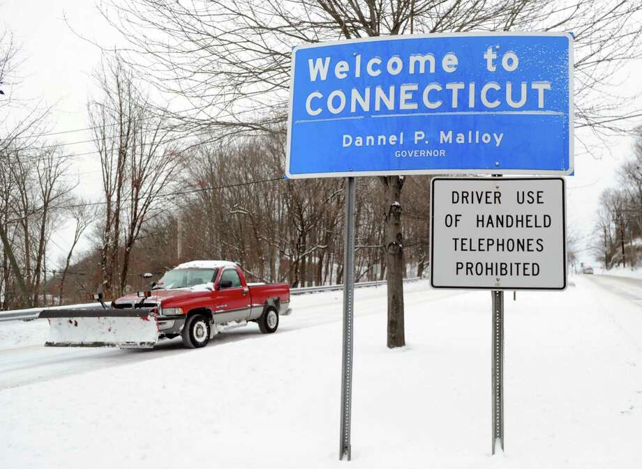 "A plow truck passes by the ""Welcome to Connecticut"" sign on West Putnam Avenue during the snow storm that hit Greenwich, Conn., Friday morning, Jan. 3, 2014. Photo: Bob Luckey / Greenwich Time"