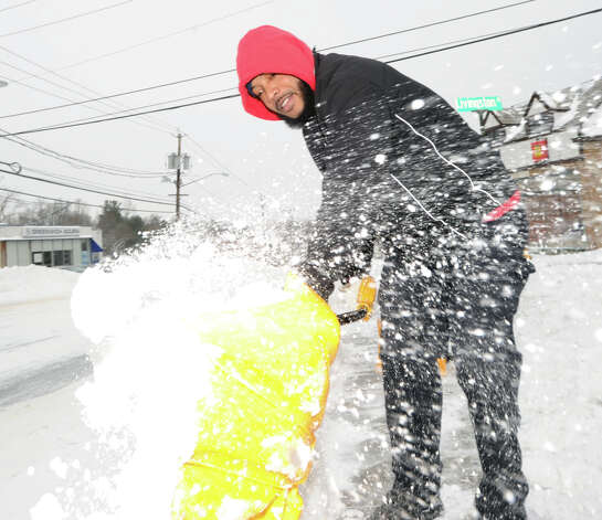Isaac Franco of Miller Motorcars shovels snow from in front of the dealership on West Putnam Avenue in Greenwich during the snow storm that hit Greenwich, Conn., Friday morning, Jan. 3, 2014. Photo: Bob Luckey / Greenwich Time