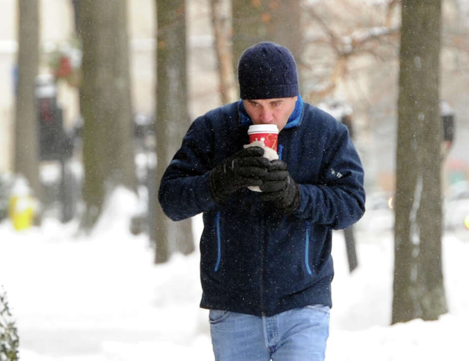 A man drinks from a cup while walking on Greenwich Avenue during the snow storm that hit Greenwich, Conn., Friday morning, Jan. 3, 2014. Photo: Bob Luckey / Greenwich Time