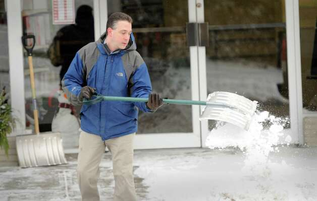 Evan Grannick shovels snow from in front of his store, Grannick's Pharmacy, on Greenwich Avenue, during the snow storm that hit Greenwich, Conn., Friday morning, Jan. 3, 2014. Photo: Bob Luckey / Greenwich Time