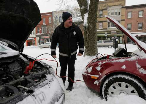 Albany firefighter Chris Kollias helps motorists jump start a vehicle on Friday, Jan. 3, 2014, in Albany, N.Y. The National Weather Service has posted winter storm warnings through Friday morning in most of the state. Temperatures are in the single digits or below zero, with the wind making it feel as cold as 20-30 below zero in some areas. Photo: Mike Groll, AP / AP