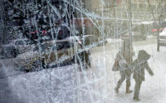 Ice crystals form on an abandoned store's front window in Syracuse, N.Y., Thursday, Jan. 2, 2014. New York City public schools were closed Friday after up to 7 inches of snow fell by morning in the first snowstorm of the winter. Photo: Mike Greenlar, AP / The Syracuse Newspapers