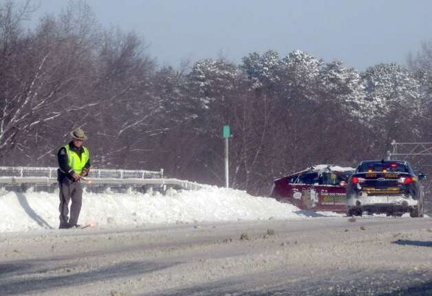 A New York State trooper puts down flares as he assists a motorist who slid of the I-87 on Friday Jan. 3, 2014 in Colonie , N.Y. (Michael P. Farrell/Times Union) Photo: Michael P. Farrell / 00025215A