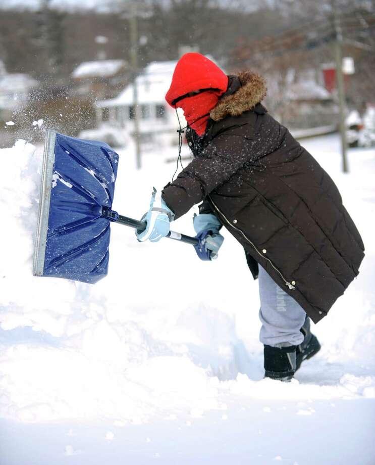Michelle Reyes shovels a neighbor's sidewalk in Derby, Conn. Friday, Jan. 3, 2014. Photo: Autumn Driscoll / Connecticut Post