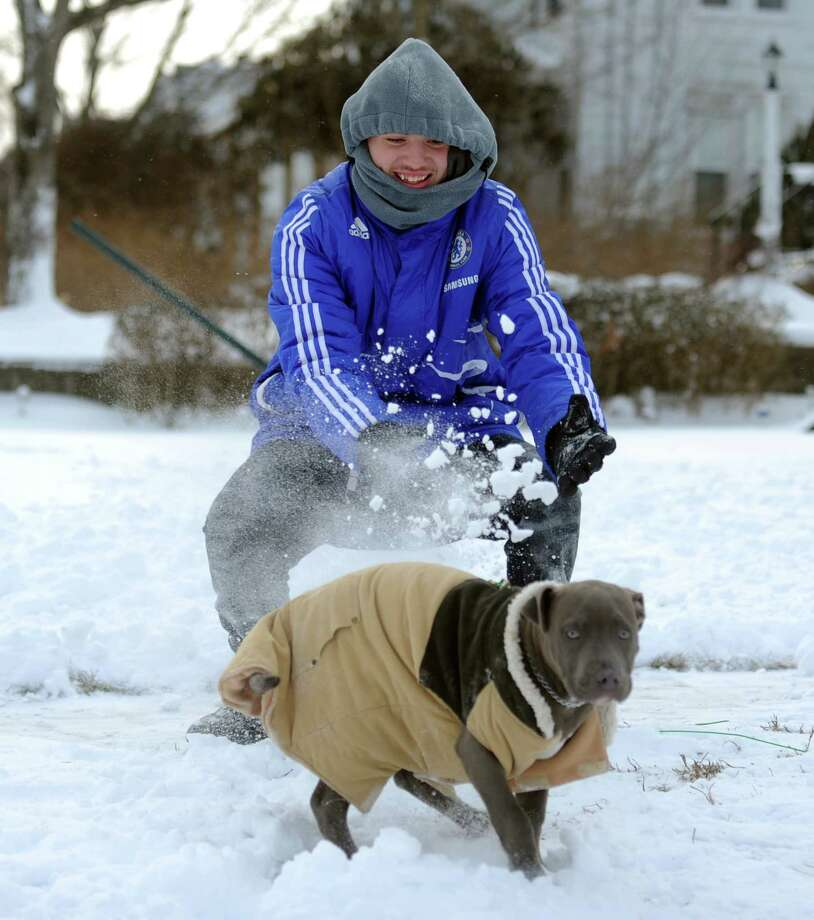 Eighteen-year-old Tharon Reyes takes a break from snow cleanup to play with his dog at his home in Derby, Conn. Friday, Jan. 3, 2014. Photo: Autumn Driscoll / Connecticut Post