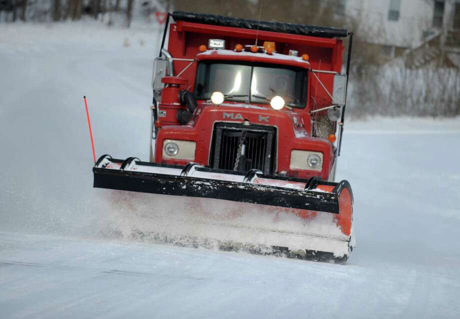 A plow truck clears snow from the road in Derby, Conn. Friday, Jan. 3, 2014. Photo: Autumn Driscoll / Connecticut Post
