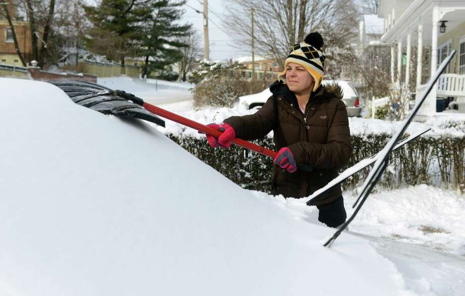 Karlee Schumacher clears the snow from her car in Ansonia, Conn. Friday, Jan. 3, 2014. Photo: Autumn Driscoll / Connecticut Post
