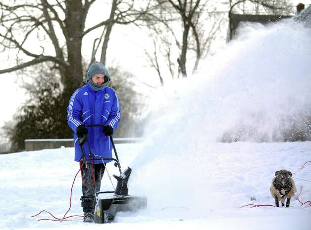 Eighteen-year-old Tharon Reyes clears snow from his driveway in Derby, Conn. Friday, Jan. 3, 2014. Photo: Autumn Driscoll / Connecticut Post