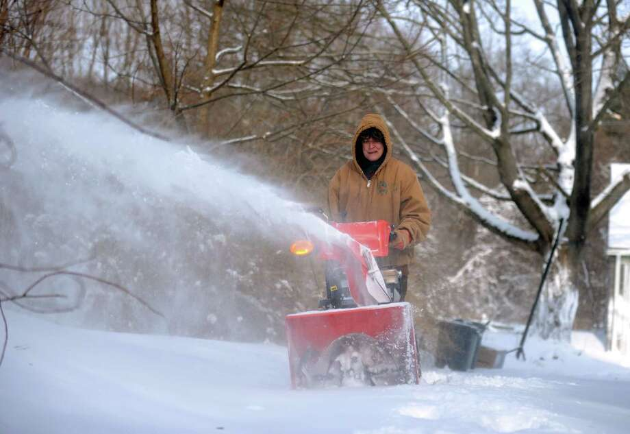 A woman uses a snowblower to clear her driveway in Derby, Conn. Friday, Jan. 3, 2014. Photo: Autumn Driscoll / Connecticut Post