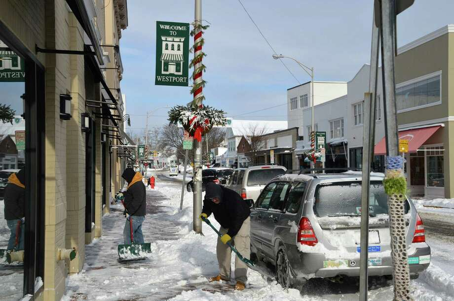 Shovelers all over downtown on Friday tackled the carpet of 5 to 7 inches of snow dropped on the town overnight to get ready for business. Photo: Jarret Liotta / Westport News contributed