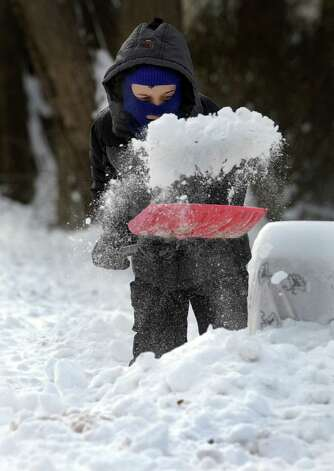 Ashton Capichiano, 12, helps his family shovel the walks and drive at their home on Curtis Avenue in New Fairfield, Conn. after an overnight snowfall, Friday, Jan. 3, 2014. Photo: Carol Kaliff / The News-Times