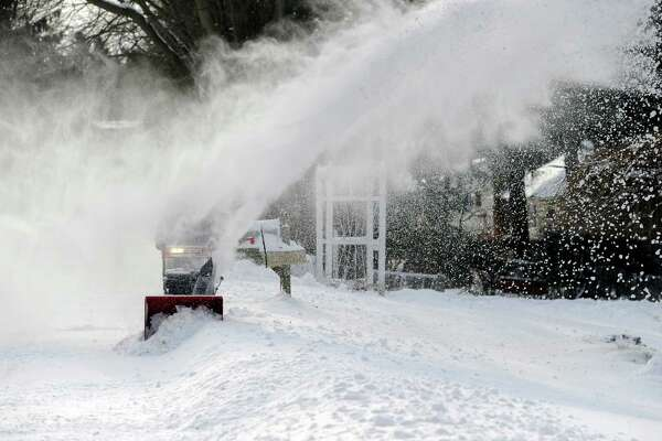 Paul Capichiano's sight is obscured by the blowing snow as he clears his property on Curtis Avenue in New Fairfield, Friday, Jan. 3, 2014.