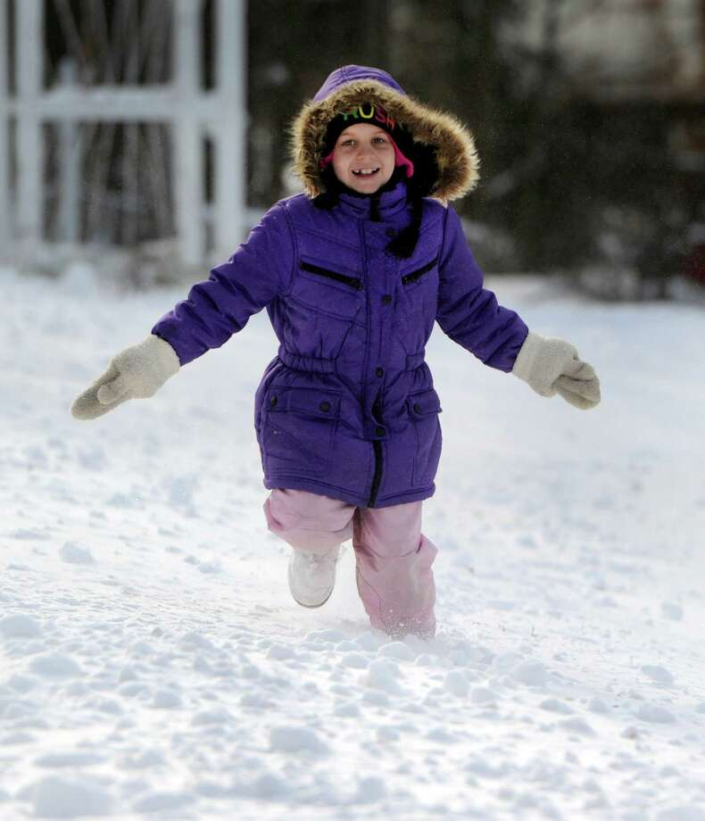 Kayleigh Capichiano, 12, runs in the snow at her home on Curtis Avenue in New Fairfield, Conn., after an overnight snowfall, Friday, Jan. 3, 2014. Photo: Carol Kaliff / The News-Times