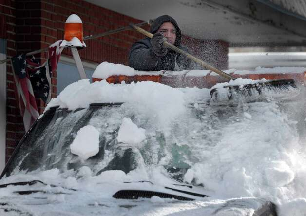 Oscar Rea, an employee of Lusio's Garage on West and Beaver Streets in Danbury, Conn., clears snow from one of the company's trucks after an overnight snowfall, Friday, Jan. 3, 2014. Photo: Carol Kaliff / The News-Times