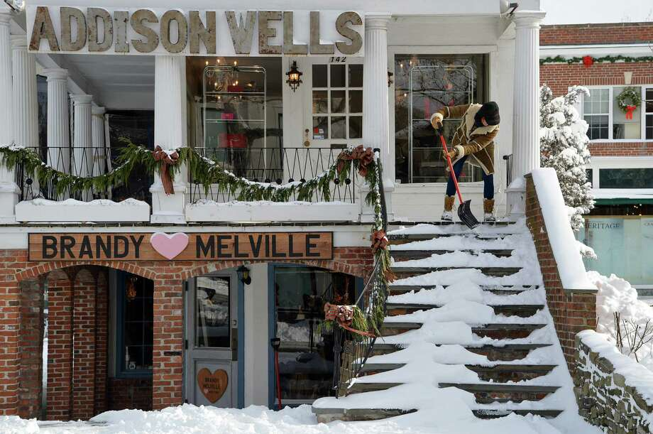 Jocelyn Armstrong of Addison Wells proved to have strong arms Friday in shoveling snow off the steps of the downtown Westport store. Photo: Jarret Liotta / Westport News contributed