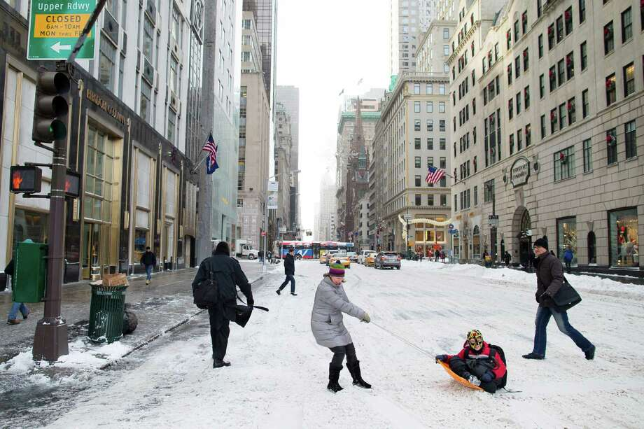 Liam Necina is pulled along in a snow sled on 58th Street by his mother Noreen, Friday, Jan. 3, 2014, in New York. New York City public schools were closed Friday after up to 7 inches of snow fell by morning in the first snowstorm of the winter. Photo: John Minchillo, AP / FR170537 AP