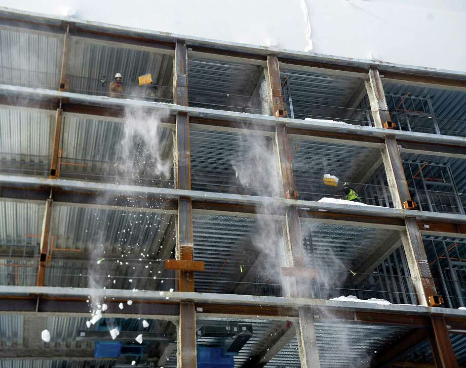 Construction workers shovel snow off upper levels of new construction on Summer Street in Stamford, Conn., on Friday, January 3, 2014. Photo: Lindsay Perry / Stamford Advocate