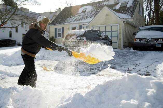 Mike Hauser shovels snow on Riverside Ave.in Stamford, Conn., on Friday, January 3, 2014. Photo: Lindsay Perry / Stamford Advocate