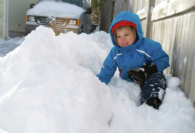 Kailer Hauser, 5, digs a hole in the snow on Riverside Ave. in Stamford, Conn., on Friday, January 3, 2014. Photo: Lindsay Perry / Stamford Advocate