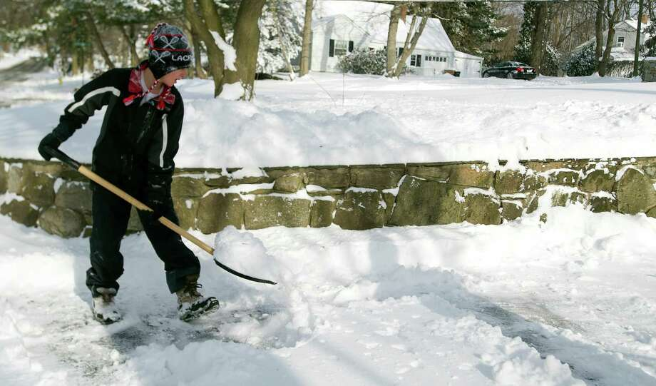 Finn O'Connor, 12, shovels snow on Pepper Ridge Road in Stamford, Conn., on Friday, January 3, 2014. Photo: Lindsay Perry / Stamford Advocate