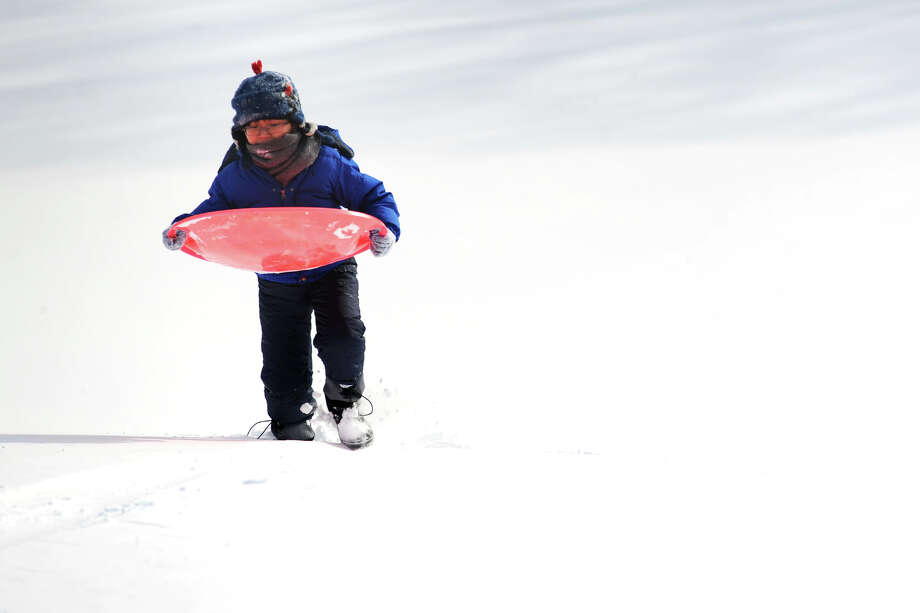 Benjamin Norodom, 10, of Orange sleds at Boothe Memorial Park following an overnight snowfall in Stratford, Conn., Jan. 3, 2014. Photo: Ned Gerard / Connecticut Post