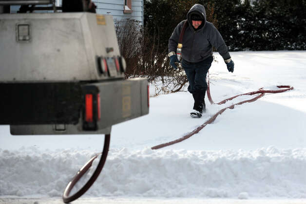 Ken Jasko, from Hoffman Energy, delivers heating oil to a home on Edison Street following an overnight snowfall in Stratford, Conn., Jan. 3, 2014. Photo: Ned Gerard / Connecticut Post