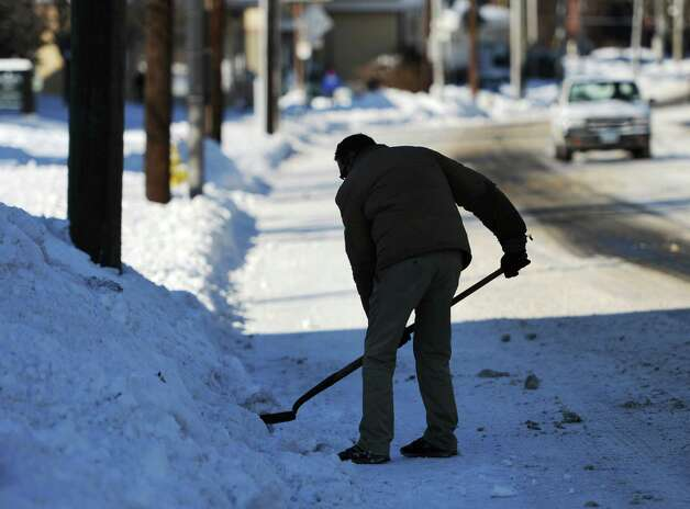 Bill Prescott, of Danbury, shovels snow along Main Street in Danbury, Conn. on Friday, Jan. 3, 2014.  Snowfall across the state ranged from 4 inches in Oxford to 9.5 inches in Milford and Darien with temperatures in the single digits and wind chill well below zero. Photo: Tyler Sizemore / The News-Times