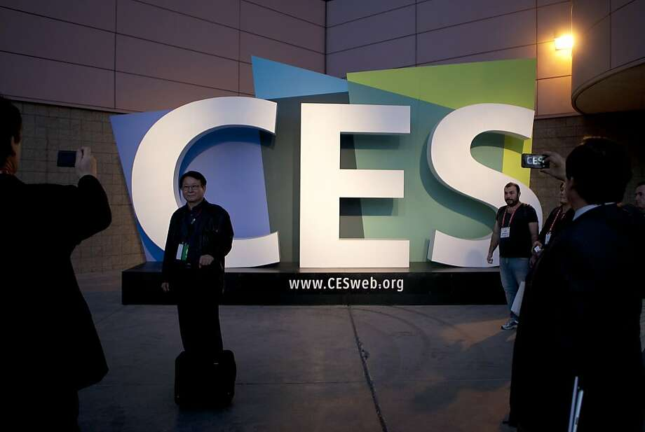 Attendees take photographs of the CES sign outside the event last January. About 152,000 are expected this year. Photo: Andrew Harrer, Bloomberg