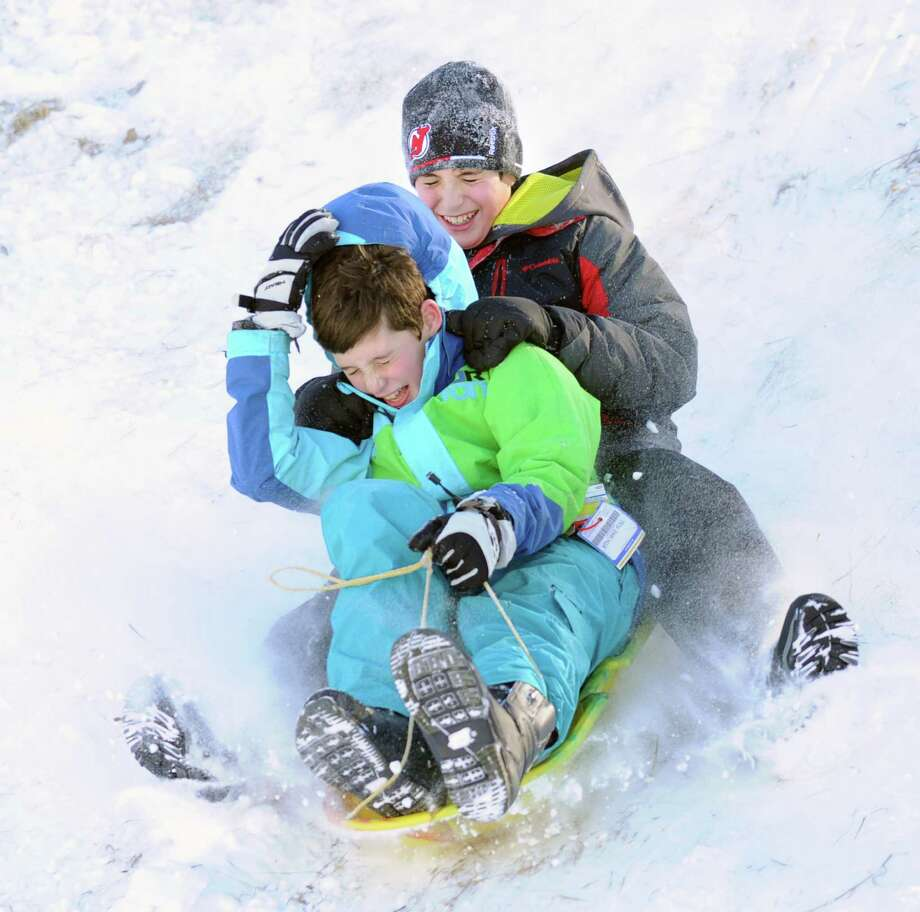 At front, Jack Capizzi, and Ben Presley, both 11, both of Greenwich, sled ride at the Western Greeenwich Civic Center, Greenwich, Conn., Friday afternnon, Jan. 3, 2014, during the aftermath of the snow storm that hit the area. Photo: Bob Luckey / Greenwich Time