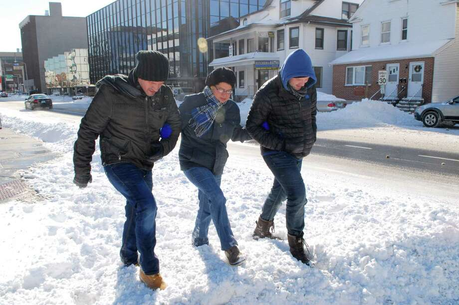 Stamford, Conn. residents Nicholas Ortiz, Sandra Vega and Jerrod Blair walk up Summer St to the grocery store on Friday January 3, 2013. Photo: Dru Nadler / Stamford Advocate Freelance