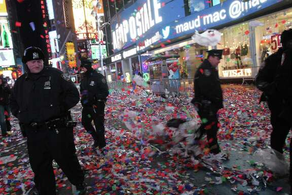 The party's over: New York police officers walk through confetti and other debris in Times Square in the early hours of New Year's Day. Crowd estimates varied wildly.