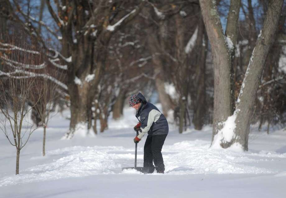 A Newtown man shovels the sidewalk along Main Street in Newtown Friday. Photo: Tyler Sizemore, Danbury News-Times
