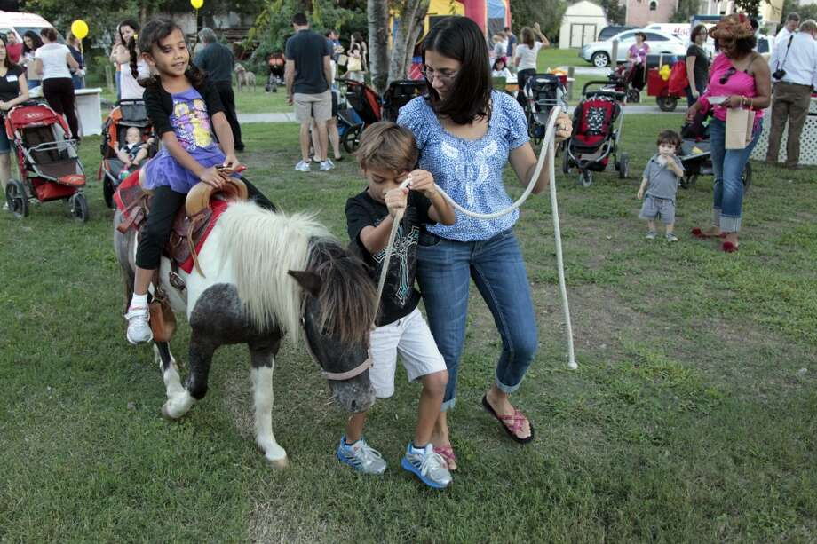 Six year-old Alonbra Fernandez rides a pony as her brother eight year-old Andres Cave and mother Esther Cruz pull her along during National Night Out. The event was held  at Nellie Keyes Park in the Rice Military neighborhood near Washington Avenue in 2012. Photo: Billy Smith II, Houston Chronicle
