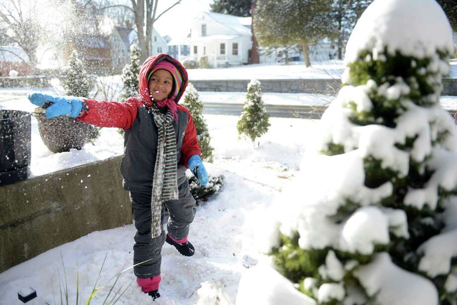 Seven-year-old Caroline Ruiz-Robinson throws snowballs at the front window of her house in Ansonia, Conn. Friday, Jan. 3, 2014 while her mother shovels the driveway. Photo: Autumn Driscoll / Connecticut Post