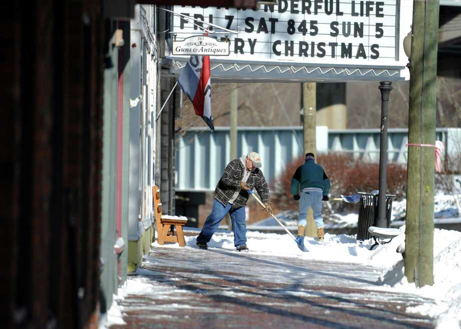 Building owner Pete Giovacchino shovels the sidewalk on Main Street in Seymour, Conn. Friday, Jan. 3, 2014. Photo: Autumn Driscoll / Connecticut Post