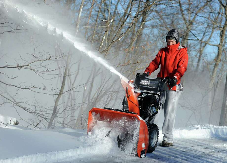 Greg Sczaplicki uses a snowblower to clear the driveway at his home in Oxford, Conn. Friday, Jan. 3, 2014. Photo: Autumn Driscoll / Connecticut Post
