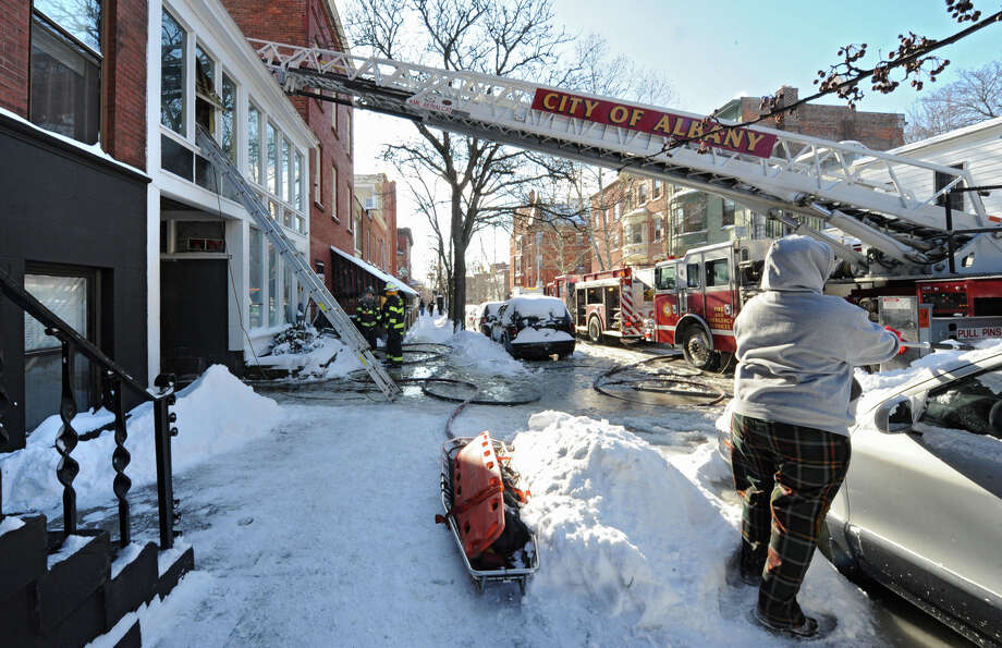 Firefighters finish putting out hot spots at the scene of a fatal fire at at 28 Dove St. on Friday, Jan. 3, 2014 in Albany, N.Y.  A 47-year-old man died of smoke inhalation due to the fire early Friday afternoon, according to a city fire official. (Lori Van Buren / Times Union) Photo: Lori Van Buren