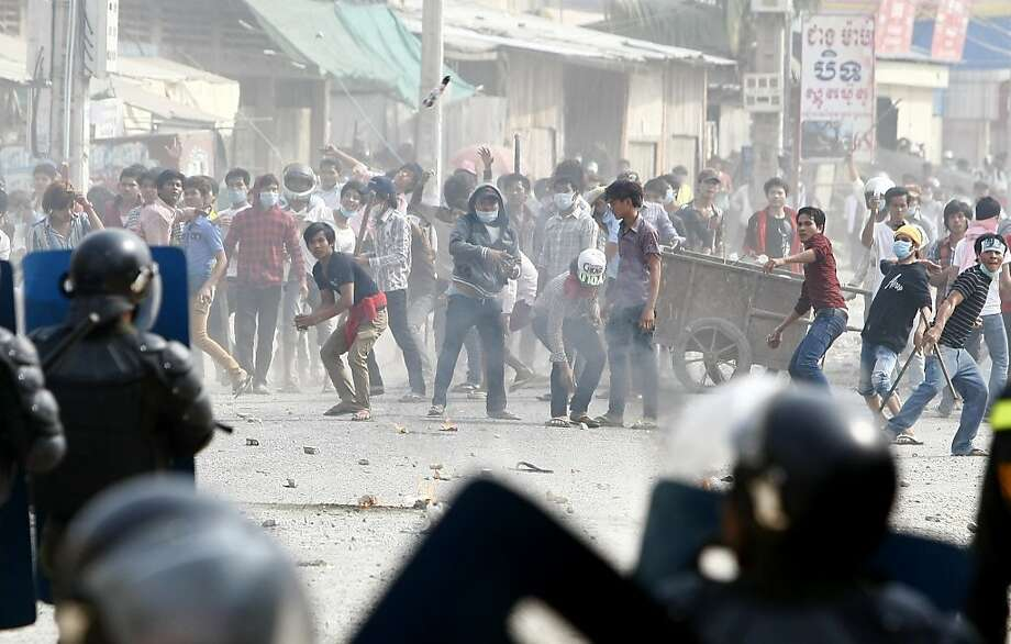 Garment workers throw objects at riot police during a strike in a Phnom Penh suburb. Photo: Heng Sinith, Associated Press