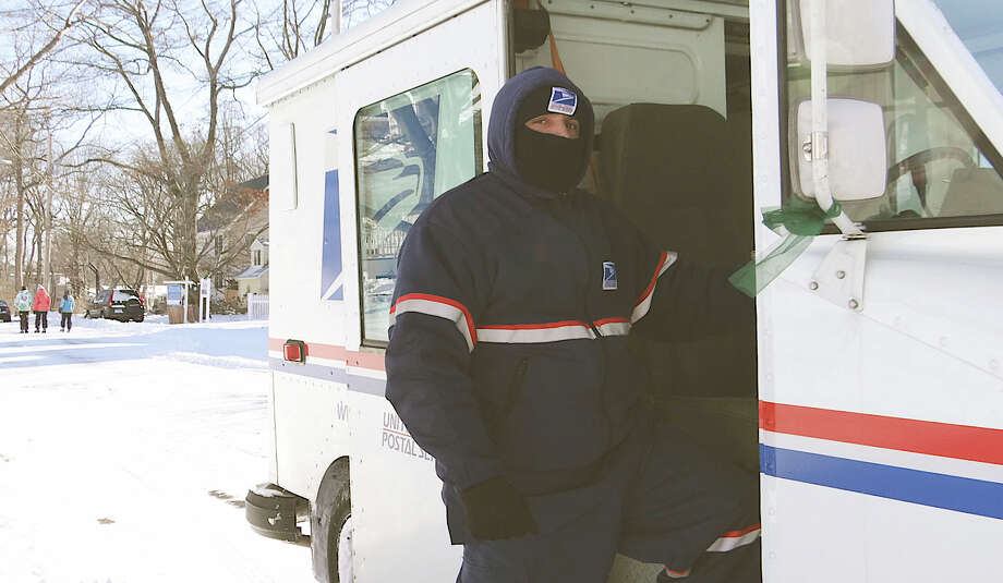 Postal carrier Jose Segui is bundled against Friday's frigid weather as he makes his appointed rounds through new snow in the town's beach area. Photo: Mike Lauterborn / Fairfield Citizen contributed