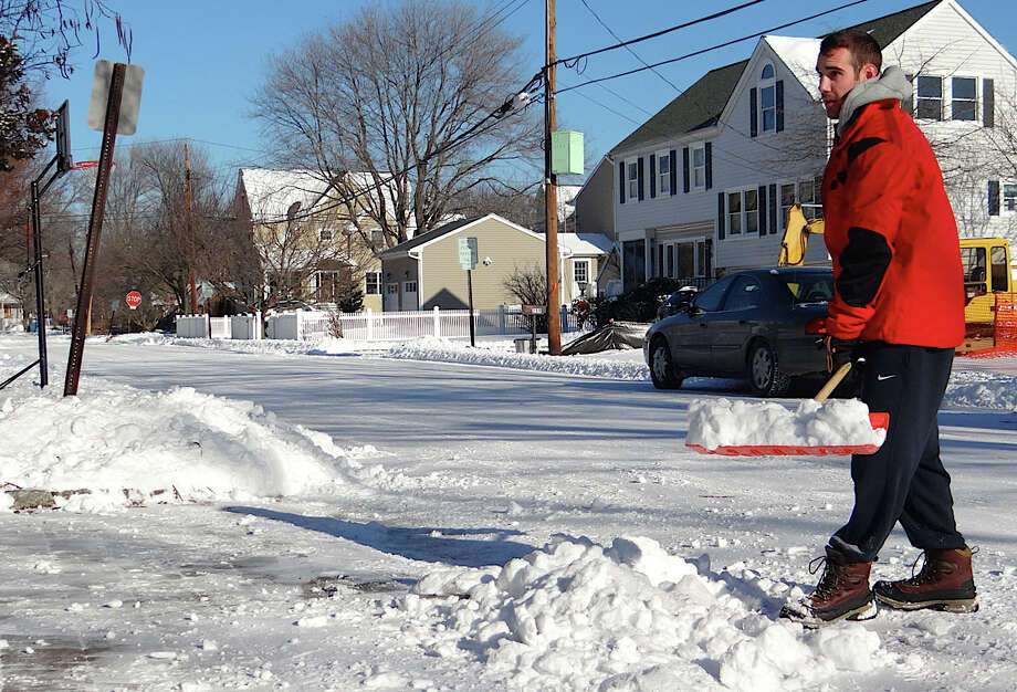 David Avallon finishes shoveling his driveway on Edward Street on Friday after a blanket of 5 to 7 inches of snow fell on town overnight. Photo: Mike Lauterborn / Fairfield Citizen contributed