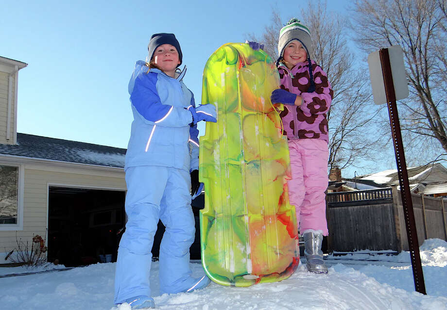 Katie Pulsifer and Avery McMahan, both 7, fashioned their own sledding slope Friday on Birch Road. Photo: Mike Lauterborn / Fairfield Citizen contributed