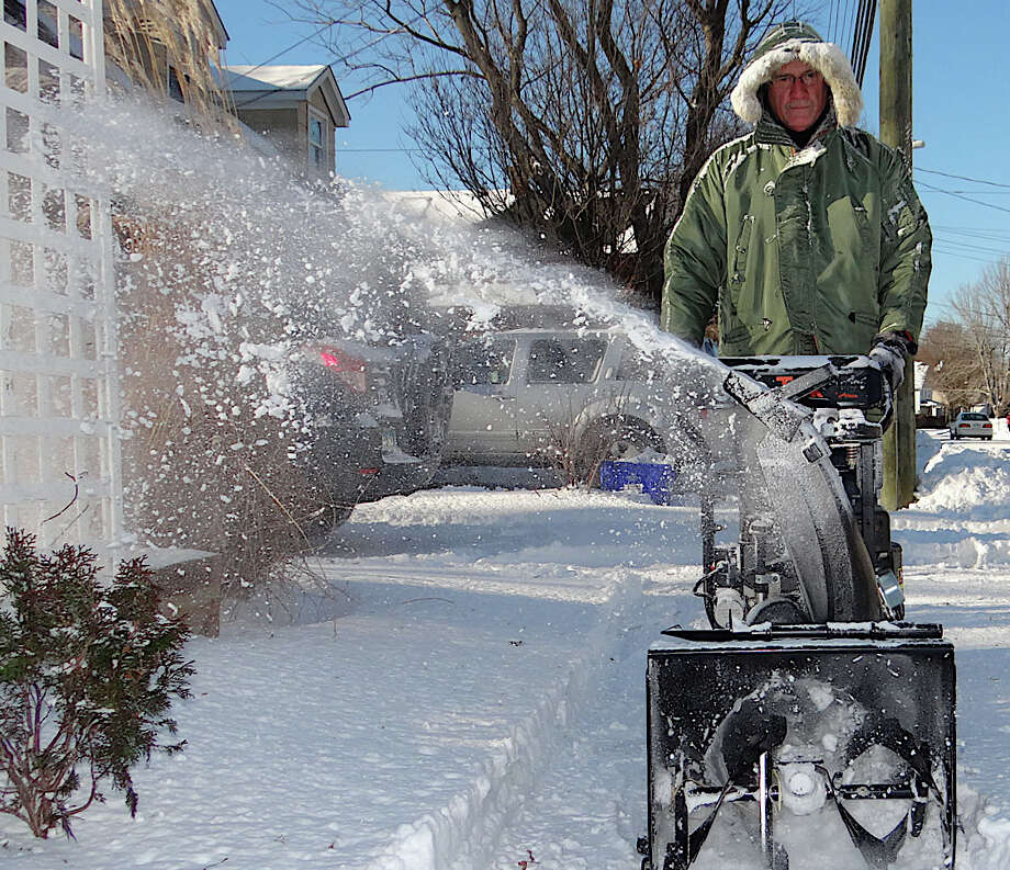 Mike Calloway plows through new snow Friday that fell overnight from the sidewalk in front of his Reef Road home. Photo: Mike Lauterborn / Fairfield Citizen contributed