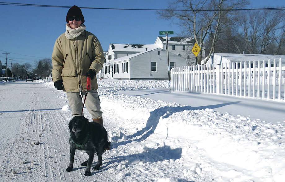 Ilse Martin walks her dog Celine along Reef Road near Bud's Deli on a snow-bright Friday afternoon. Photo: Mike Lauterborn / Fairfield Citizen contributed