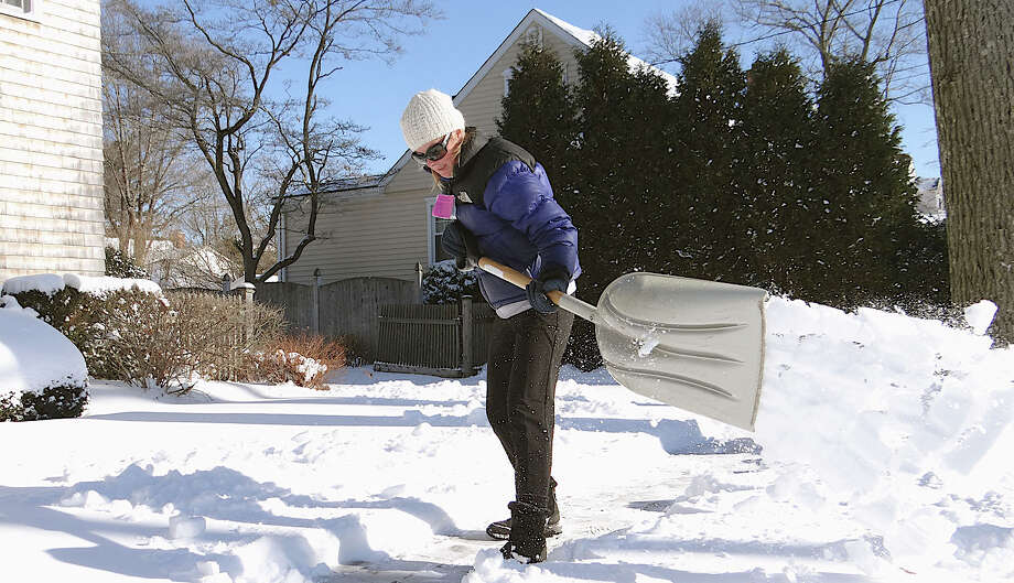 Elizabeth Childers shovels a neighbor's walkway on Dwight Street on Friday after the overnight snow. Photo: Mike Lauterborn / Fairfield Citizen contributed